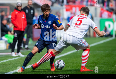 Cologne, Germany. 31st Mar, 2019.  Soccer: 2nd Bundesliga, 1st FC Cologne - Holstein Kiel, 27th matchday in the Rhein-Energie-Stadion. Kiel's Masaya Okugawa (l) and Cologne's Rafael Czichos fight for the ball. Photo: Guido Kirchner/dpa - IMPORTANT NOTE: In accordance with the requirements of the DFL Deutsche Fußball Liga or the DFB Deutscher Fußball-Bund, it is prohibited to use or have used photographs taken in the stadium and/or the match in the form of sequence images and/or video-like photo sequences. Credit: dpa picture alliance/Alamy Live News - Stock Photo