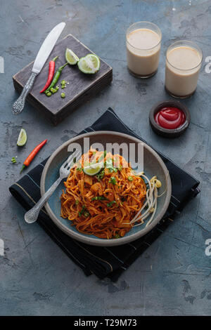 Spicy asian mee goreng mamak with eggs, ketchup and chili, top view. - Stock Photo