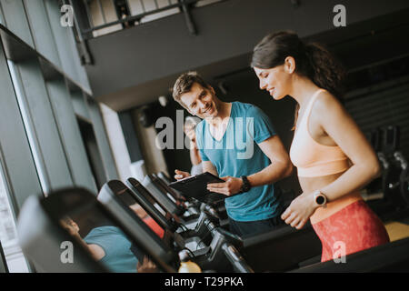 Young woman with trainer working out on treadmill in gym