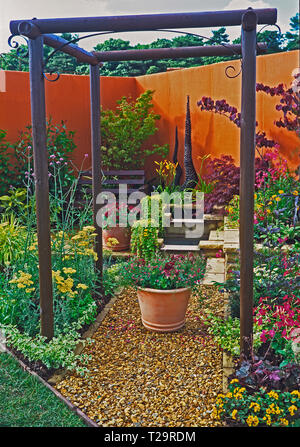 A colourful urban show garden with planted containers of flowers and a seating area - Stock Photo