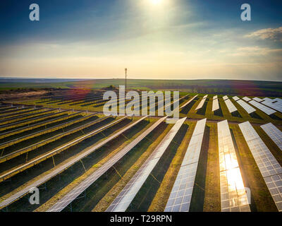 Solar panel produces green, environmentaly friendly energy from the setting sun. Aerial view from drone. Landscape picture of a solar plant