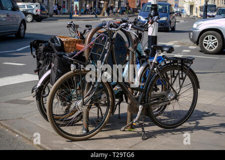 Devizes, Wiltshire, England, UK, March 2019. Two tourists bicycles padlocked to a secure stand on Market Square Devizes. - Stock Photo