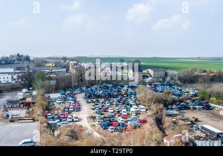 Lines of crushed cars wreck - in scrapyard before being shredded recyling - Stock Photo