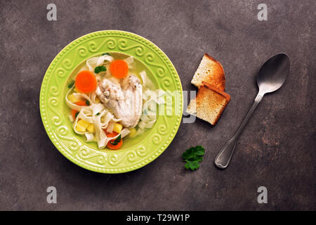 Chicken noodle soup, potatoes, carrots in a green plate served with fried toasts on a dark rustic background. Top view, copy space - Stock Photo