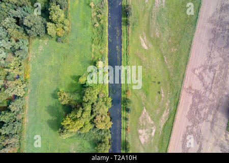 Aerial image of the Niers besides trees and meadows landscape in West Germany - Stock Photo