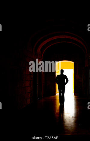 Lone figure, silhouetted, walking through a dark corridor. - Stock Photo