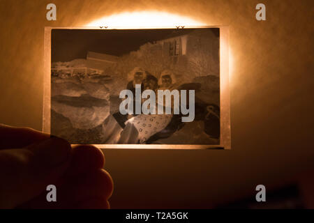 hand holding old black and white negative up to light,of two women,on,breach,Gurnard,Isle of Wight, England, UK, - Stock Photo
