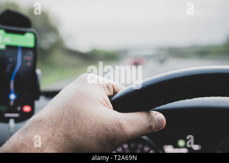 Google maps on a smart phone attached to holder on the windsceen of a car - seen by the driver - with a view of hands on steering wheel. - Stock Photo