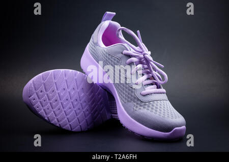 Unbranded purple running shoes on a black background - Stock Photo