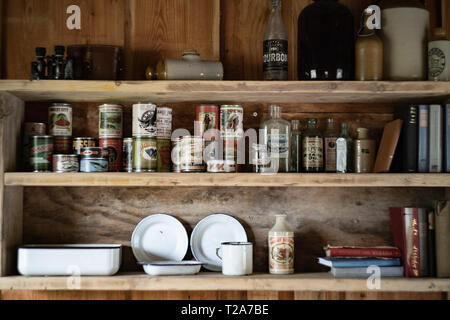 Shelf with old / traditional North American food tins and bottles on a shelf in a trapper's hut / cabin - Stock Photo