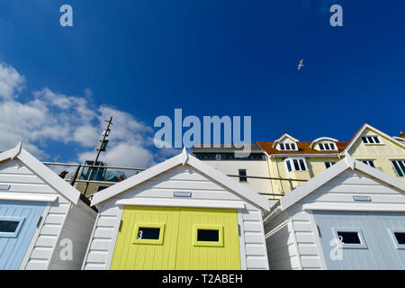 UK .Brightly coloured Beach Huts against a deep blue sky with light white clouds and a lone seagull in flight on the promenade of Lyme Regis in Dorset - Stock Photo