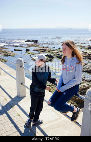 Bother and sister on the Sea Point Promenade. - Stock Photo