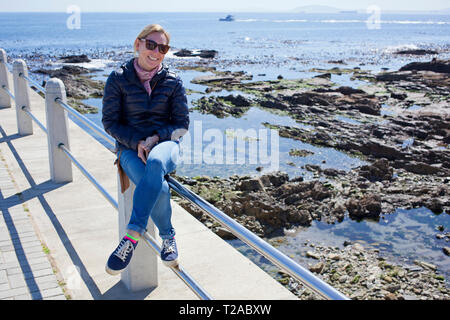 Woman sitting on railing along Sea Point Promenade, Cape Town - Stock Photo