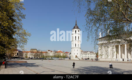 Vilnius, Lithuania - May 6, 2017: People on the Cathedral square against bell tower of Vilnius Cathedral. Bell tower was erected on remains of earlier - Stock Photo