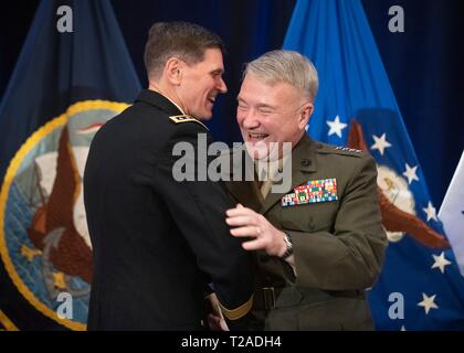 The outgoing commander of U.S. Central Command, General Joseph L. Votel, embraces his replacement Marine Corps Gen. Frank McKenzie, right, during his retirement ceremony at Macdill Air Force Base March 29, 2019 in Tampa, Florida. Votel retired after 39 years of military service. - Stock Photo
