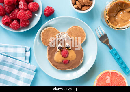 Pancake in shape of a bear for kids on blue plate. Healthy colorful breakfast for children. Top view - Stock Photo