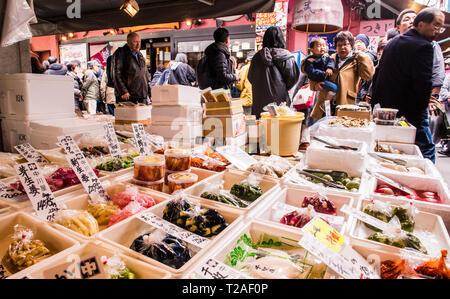 Display of fresh food on display and people walking through market, Tsukiji Fish market, Tokyo, Japan