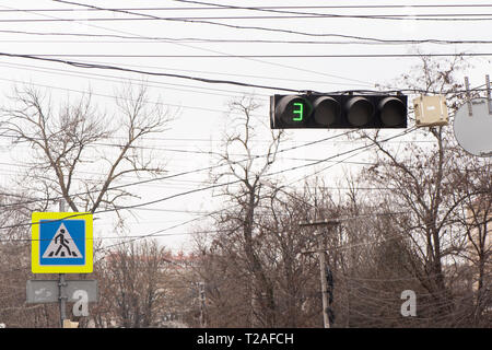 traffic light glowing green. The next color is 3 seconds away. Also in the background there is a sign of a pedestrian crossing. - Stock Photo