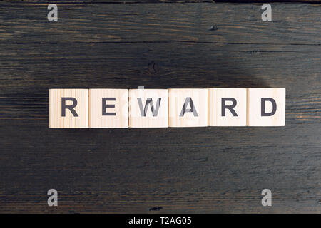 Word REWARD written on a wooden cube. Risk and reward concept - Stock Photo