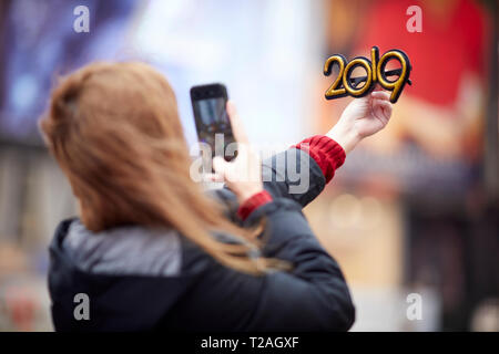 New York Manhattan tourist posing with a 2019 hew year glasses  in Times Square USA - Stock Photo