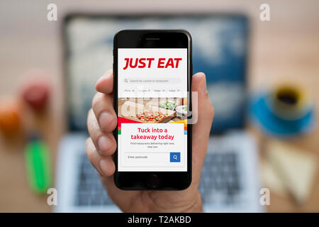 A man looks at his iPhone which displays the Just Eat logo (Editorial use only). - Stock Photo