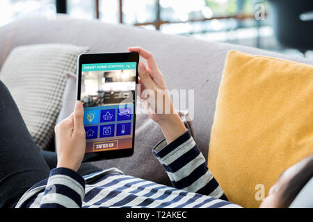 Smart home automation control concpet.Woman lying down on sofa using tablet control device in home.digital technology lifestyle. - Stock Photo