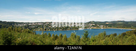 Wide view over Lake Sorpesee with sailboats and the dam with Langscheid in the background in front of a cloudy sky in Sundern, Sauerland, Germany - Stock Photo