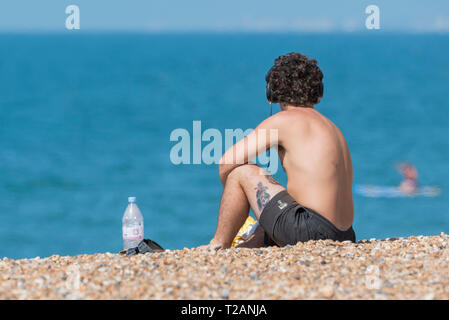 Young man sitting shirtless on a shingle beach in Summer listening to music on headphones, at the seaside in the UK. - Stock Photo