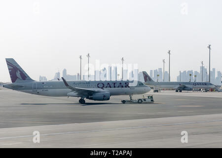 Doha, Qatar, 2018-05-01: Towing Qatar aircraft to the parking lot by TUG Pushback tractor. Ground support equipment at airport. - Stock Photo