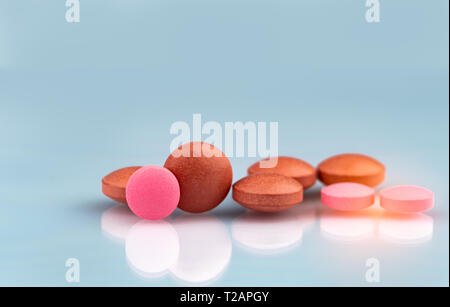 Selective focus on orange and pink round tablets with shadow on gradient background. Pharmaceutical industry. Pharmacy products. Vitamins and suppleme - Stock Photo