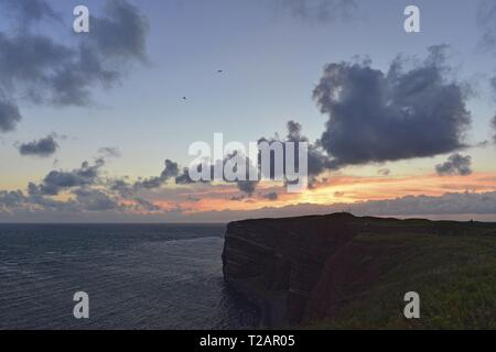 Easily cloudy colourful evening sky with the dark rocks from the island Heligoland in the North Sea, 25 June 2017 | usage worldwide - Stock Photo