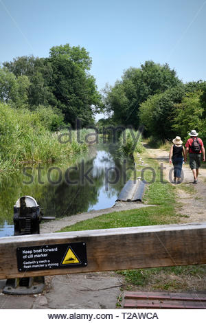 Portrait image of a middle-aged couple, wearing hats, walking along an English canal towpath, close to a lock, in bright summer sunshine. - Stock Photo
