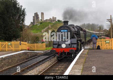 British Railways Standard Class 4 tank No. 80104, renumbered No. 80126, travelling through Corfe Castle, Dorset, UK in March - Stock Photo