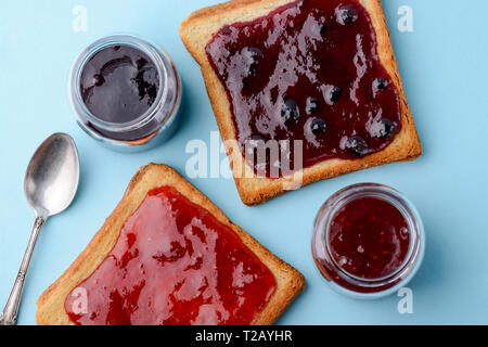 Toast with jam on blue - Stock Photo