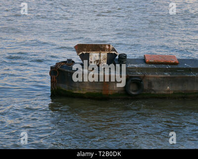 Old and rusty iron boat anchored on the Victoria  Embankment site of the River Thames, London, UK, with a skip for maintenance work on the river. - Stock Photo