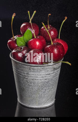 Fresh red Cherries in small metal bucket on black background, Close up, vertical composition - Image - Stock Photo