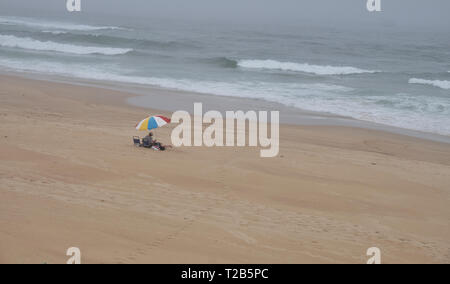 Beach with one single umbrella on a cloudy autumn day.  Desolate capture, with only couple visible under the umbrella - Stock Photo