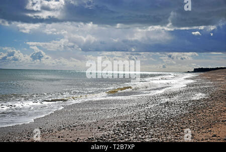 Beautiful sea view of the rough waves breaking onto the pebble beach with a dramatic cloudy sky along the Kent coastline - Stock Photo