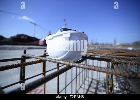 Construction worker helmet on top of a reinforcing iron on a construction site - Stock Photo