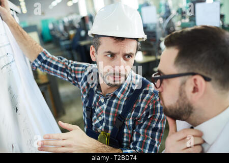 Head and shoulders  portrait of two factory workers discussing  plans and schemes standing in workshop, copy space - Stock Photo
