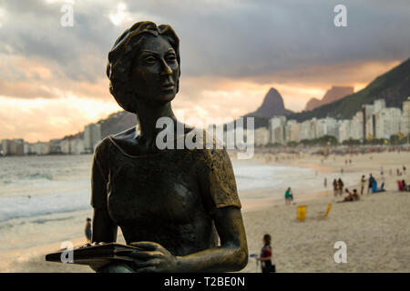 Rio de Janeiro, Brazil - March 29, 2019: Statue of the writer Clarice Lispector with her dog 'Ulisses' in the 'Fishermen's Way' with the sea in the ba - Stock Photo