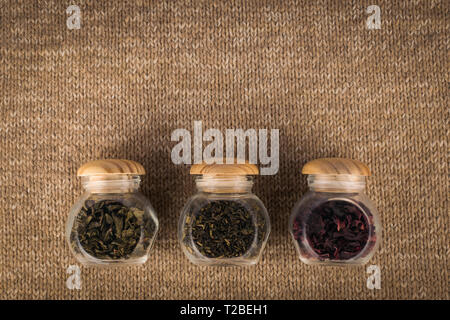 Different kinds of tea in small glass jars - Stock Photo