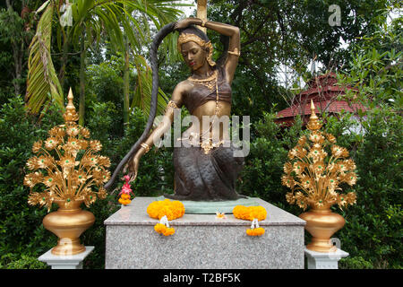 Phra Mae Thorani statue with offerings in garden at Wat Pan Ping - Stock Photo