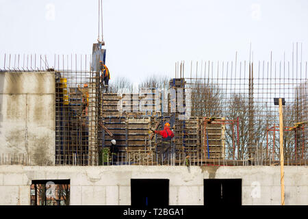 the worker and the crane operator unload the car with reinforced concrete walls for building a large wellness center with a swimming pool of modern te - Stock Photo