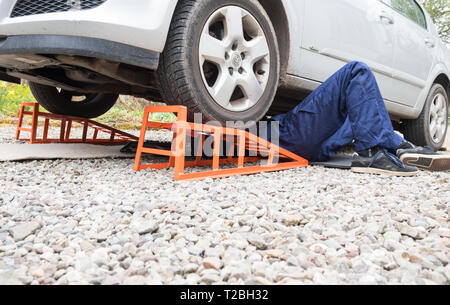 young man lying underneath his car raised up on ramps - Stock Photo