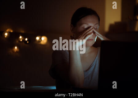 Tired woman working overtime on laptop computer at night in her home office, face is illuminated by the blue light of the screen - Stock Photo