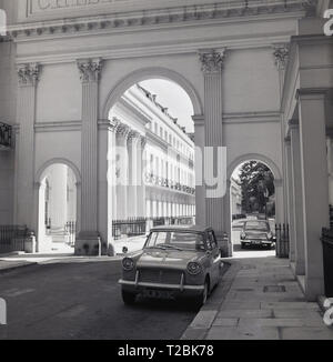 1960s, London, NW1, Grand columned entrance, a Corinthian Arch, to Chester Terrace near Regents park, with a Triumph Herald motorcar parked nearby. Chester Terrace, a neo-classical terrace, has the longest unbroken facade in Regents Park. - Stock Photo
