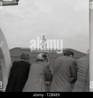 1950s, historical, people on a boat looking over the side as they pass Tilbury Riverside railway station, Thurrock, Essex, England, UK. The Empire Windrush's voyage from the Caribbean to Tilbury took place in 1948. - Stock Photo