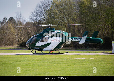 Helicopter Operating for Essex & Herts Air Ambulance Taking off from Earls Colne Aerodrome in Essex on a Fine Spring Day - Stock Photo