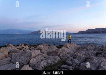 Woman wearing yellow jackets standing on rocks and looking at the sea on the coast of Baska, Krk island, Croatia - Stock Photo